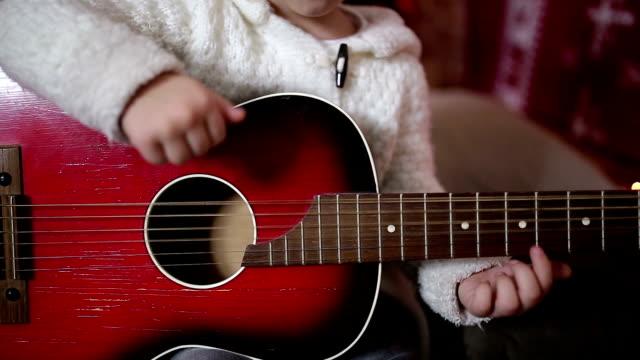 Cute little blue-eyed girl playing guitar