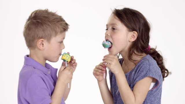 cute little boy (five-years-old) and his sister eating cake pops - sister stock videos and b-roll footage