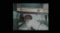 Cute little boy checks out antique television set 1960