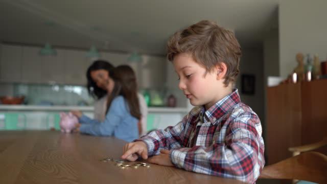 vídeos y material grabado en eventos de stock de lindo niño contando sus monedas de la alcancía mientras mamá y hermana se sentan en el fondo hablando - contar