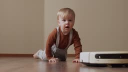 Cute little boy crawling and walking after vacuum cleaner robot. Children game at home.