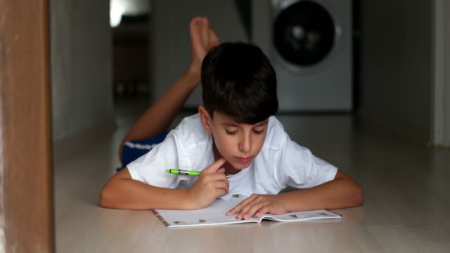 cute little boy doing his homework - quaderno video stock e b–roll