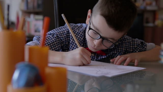 cute little boy doing his homework - eyeglasses stock videos & royalty-free footage