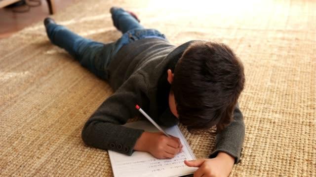 vídeos de stock, filmes e b-roll de lindo garotinho fazendo seus trabalhos de casa - batendo com a cabeça na parede