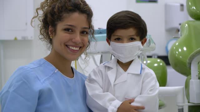 netter kleiner junge verkleidet als zahnarzt steht neben zahnarzt-assistent beide lächelnd in die kamera - zahnarzt stock-videos und b-roll-filmmaterial