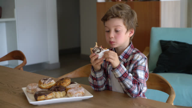 vídeos de stock e filmes b-roll de cute little boy enjoying a delicious donut at home - 8 9 anos