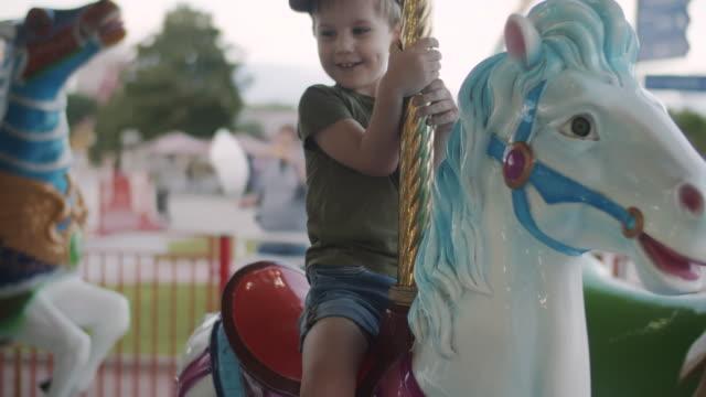 遊園地でメリーゴーランドライドを楽しむかわいい男の子 - 遊具点の映像素材/bロール