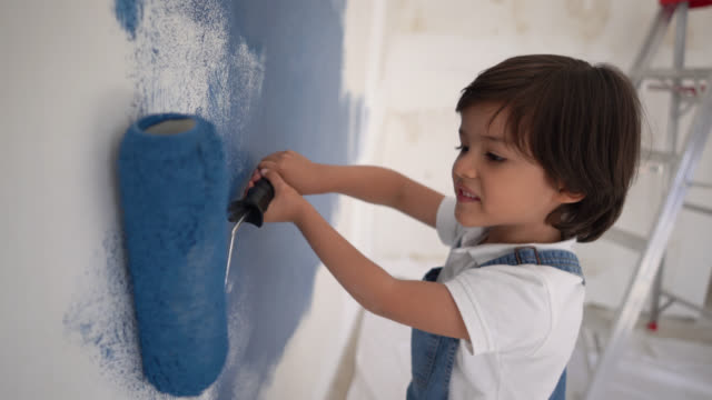 cute little boy enjoying painting with a paint roller at home smiling - diy stock videos & royalty-free footage