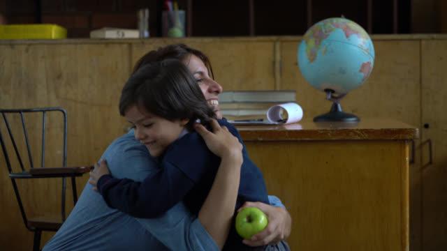 vídeos de stock e filmes b-roll de cute little boy giving a green apple and a hug to beautiful teacher - ensinar