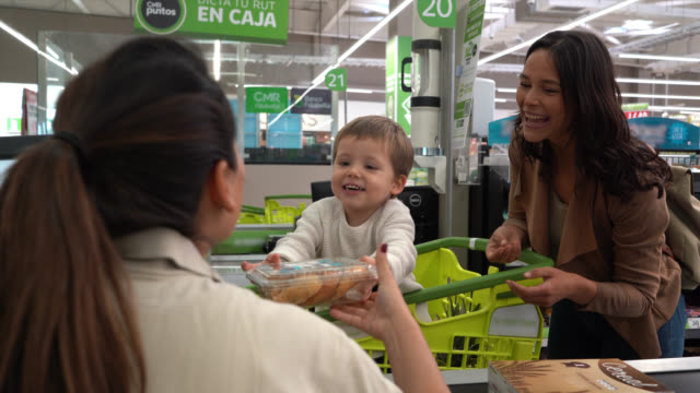 cute little boy handing products to cashier while standing in the shopping cart and mom next to him all smiling at the supermarket - checkout stock videos & royalty-free footage