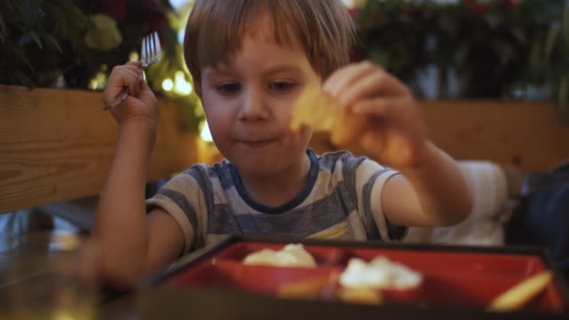 vídeos y material grabado en eventos de stock de lindo niño en un café o restaurante - pollo frito