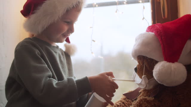 cute little boy in home quarantine playing doctor with his teddy bear on christmas - teddy boy stock videos & royalty-free footage
