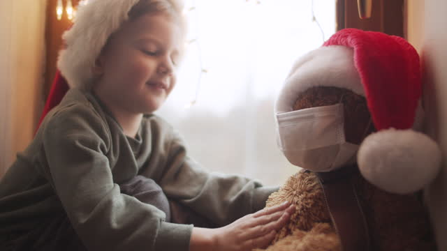 cute little boy in home quarantine putting on protective mask and santa hat on his teddy bear on christmas - teddy boy stock videos & royalty-free footage