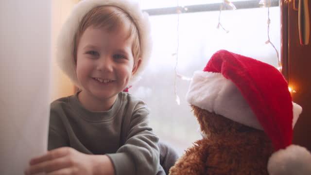 cute little boy in home quarantine with his teddy bear in santa hat on christmas - teddy boy stock videos & royalty-free footage