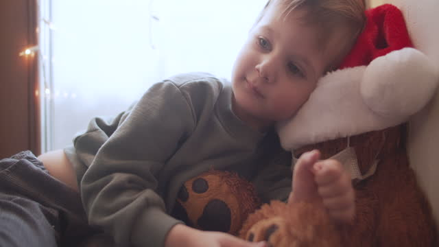 cute little boy in home quarantine with his teddy bear on christmas - advent stock videos & royalty-free footage