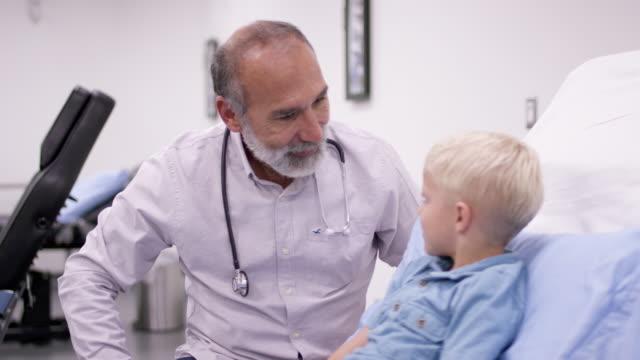 医師との医療予約でかわいい男の子 - 小児科医点の映像素材/bロール