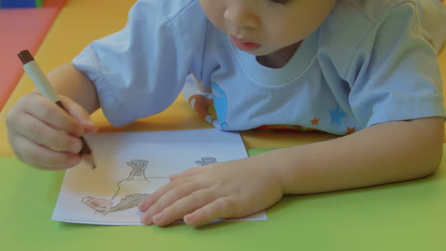 4K:A cute little boy is drawing and being creative.