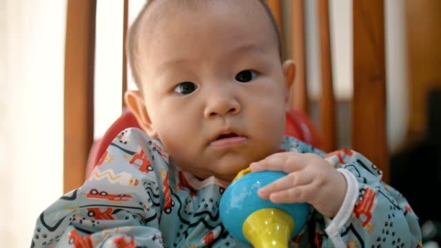 vídeos y material grabado en eventos de stock de lindo niño mirando a la cámara y sonriendo en casa - 6 11 meses