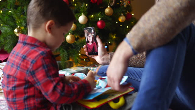 cute little boy opening a gift under a christmas tree with a parent holding a phone up so grandmother on the device can watch her grandson - christmas gift stock videos & royalty-free footage