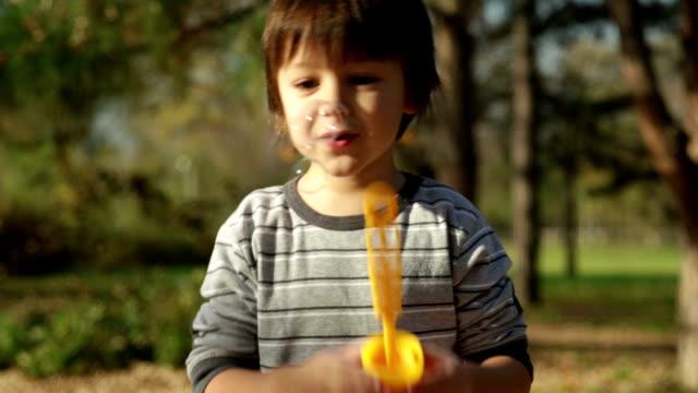 vidéos et rushes de mignon petit garçon à l'extérieur des bulles de soufflage - terrasse