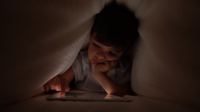 cute little boy playing with his digital tablet under the sheets lying down on tummy - digital native stock videos & royalty-free footage