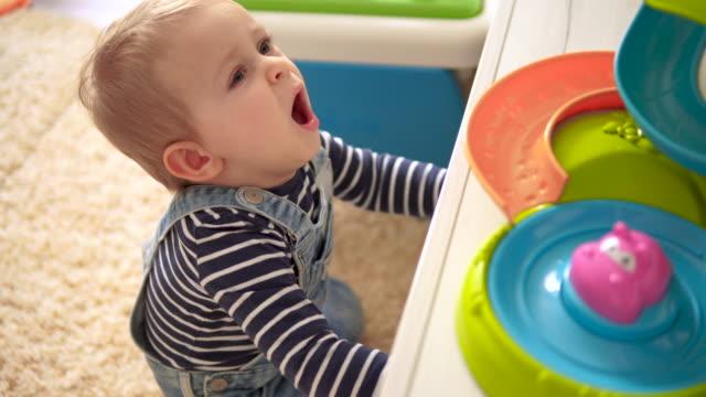 netter kleiner junge spielt mit spielzeug - ein männliches baby allein stock-videos und b-roll-filmmaterial