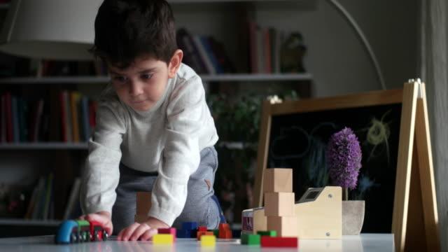 vidéos et rushes de petit garçon mignon jouant avec le train en bois - moyen oriental