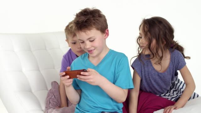 vídeos y material grabado en eventos de stock de cute little boy (seven-years-old) plays with smartphone - two friends joining him - camisa de polo
