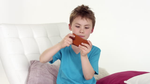 cute little boy (seven-years-old) plays with smartphone