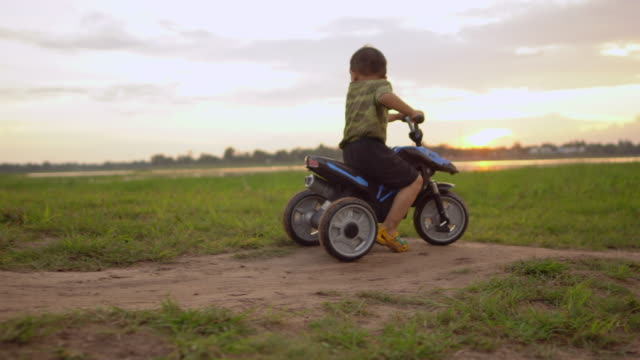 cute little boy riding tricycle in outdoors at sunset - tricycle stock videos & royalty-free footage