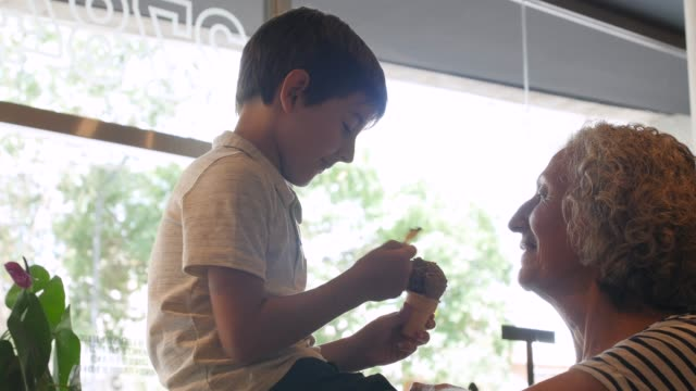 Niedlicher kleiner Junge, der sein Eis mit Großmutter teilt, während er auf der Theke in der Eisdiele sitzt