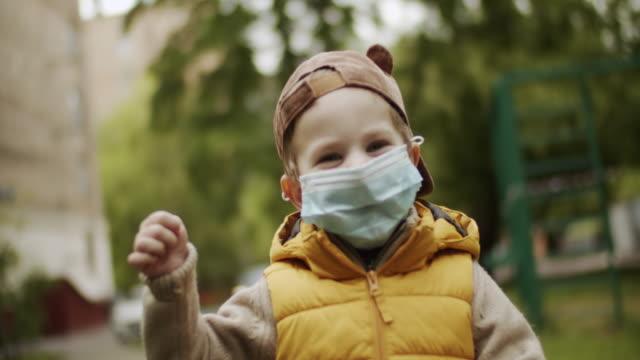 vídeos de stock e filmes b-roll de cute little boy smiling behind protective mask outdoors - responsabilidade