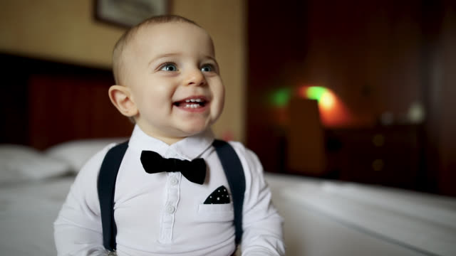 cute little boy smiling while sitting on a bed - physical stance stock videos & royalty-free footage