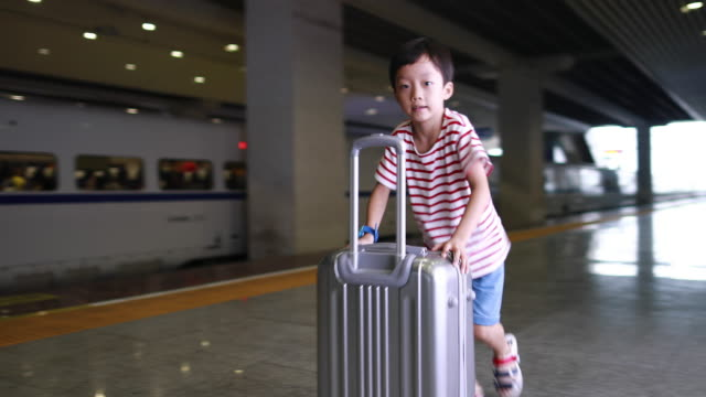 Cute little boy waiting in the railway station, child travel