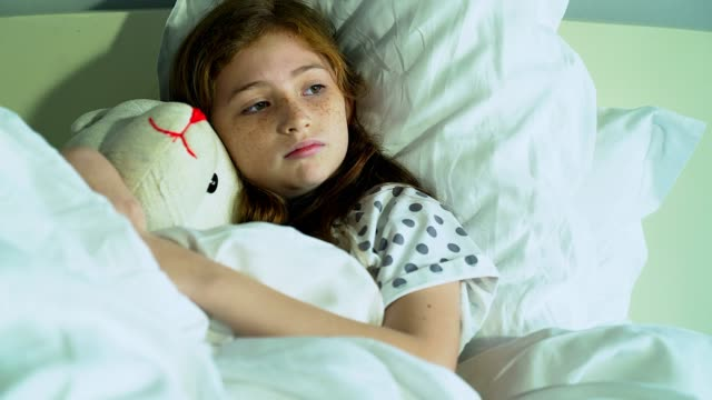 cute little child girl with her teddy bear and lying in bed with sad moody at home - innocence stock videos & royalty-free footage