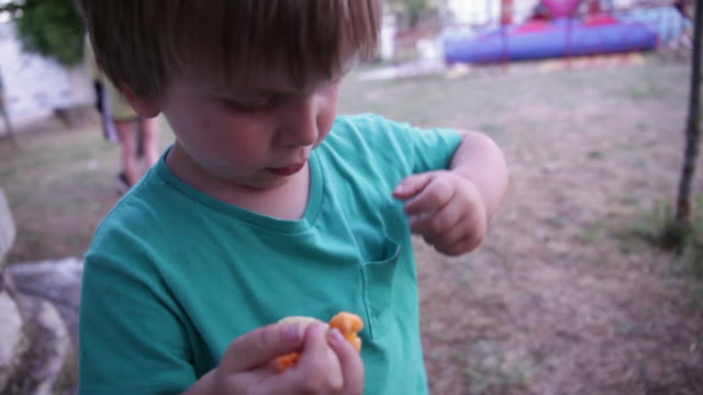 cute little child (3 years) putting some fries in his pocket. - hosentasche stock-videos und b-roll-filmmaterial