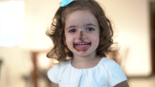 carino piccolo cioccolato ragazza ritratto a casa - antigienico video stock e b–roll