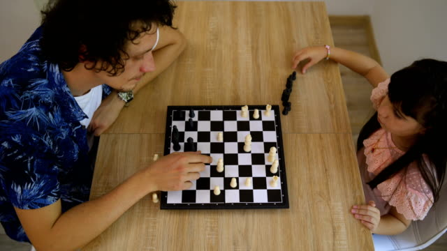 cute little daughter and her  young dad are playing chess together - board game stock videos & royalty-free footage