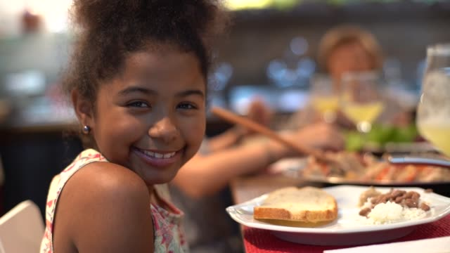 bambina carina a cena in famiglia - looking at camera video stock e b–roll