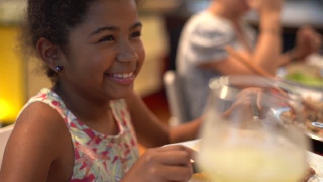 vidéos et rushes de mignonne petite fille à dîner en famille - dîner