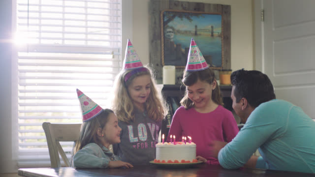 WS. Cute little girl celebrates birthday with family and friends and blows out candles on birthday cake.