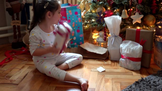 cute little girl checking what is in her gift box on christmas morning - shaking stock videos & royalty-free footage