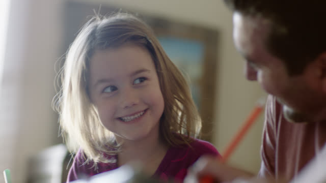 ms. cute little girl coloring with magic marker glances at her dad and smiles - homework stock videos & royalty-free footage