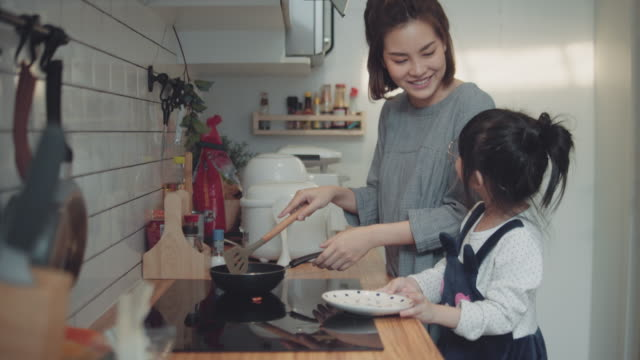 cute little girl cooking at home with mom - domestic kitchen stock videos & royalty-free footage