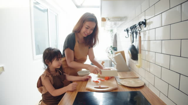 cute little girl cooking at home with mom - stereotypical homemaker stock videos & royalty-free footage