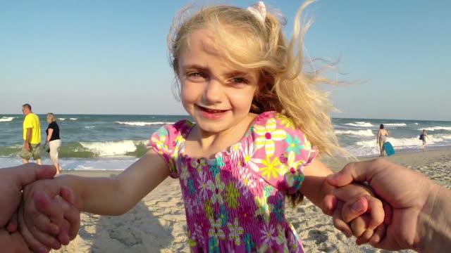 Cute little girl dances with dad on sunny beach