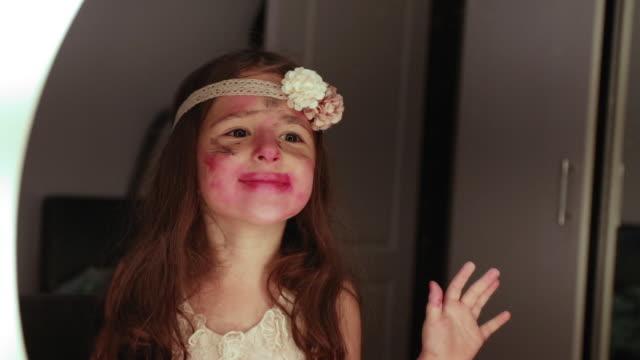 vídeos y material grabado en eventos de stock de linda niña haciendo maquillaje frente al espejo - niñas