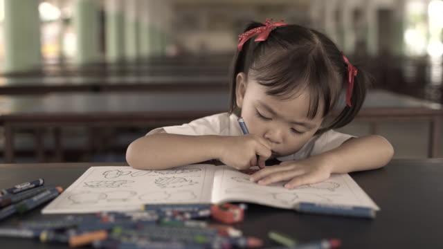 vídeos de stock e filmes b-roll de cute little girl draws with crayons - criança de escola primária
