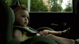 cute little girl drives with family in car child safety seat