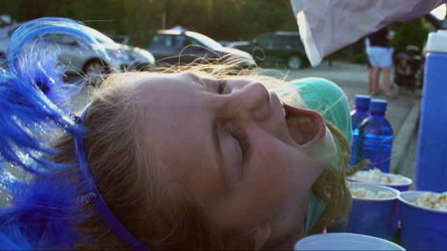 cu. cute little girl dumps popcorn on her face while tailgating with family outside sporting event. - snack stock videos & royalty-free footage
